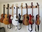 8 guitars hanging on wall