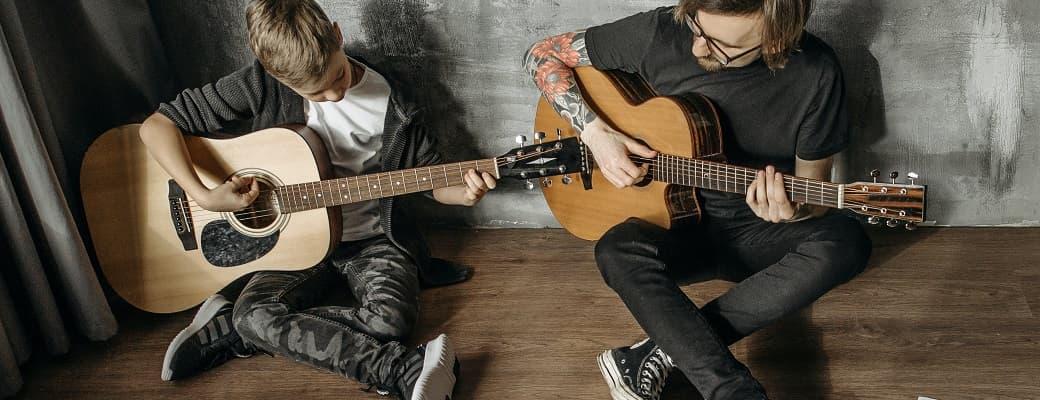 dad teaching son guitar