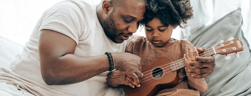 father teaching child ukulele
